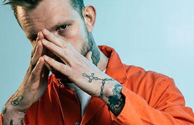 Gefangener mit Bart und roter Gefangenenkleidung schaut uns an | Hände tätowiert | Fast betende Hände vor dem Gesicht gefaltet, vielleicht zum Schutz
