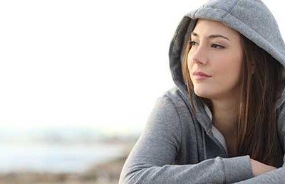 Junge Frau mit langem Harr und Sweetshirtkaputze schaut in die Weite