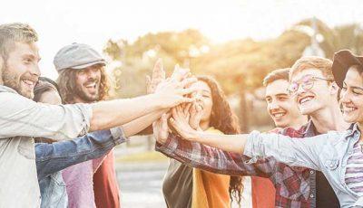 Junge Menschen reichen sich lachend die Hande