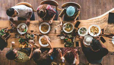 Menschen sitzen am Tisch und essen