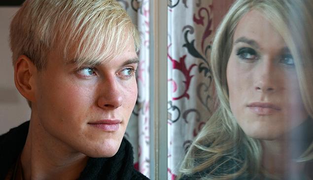 Ein Mann spiegelt sich in einer Fensterscheibe und sieht sich dort als Frau