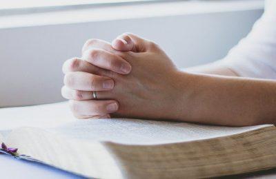 Hände gefaltet auf einer Bibel