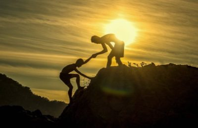 Einehilfe einem anderen den Berg hiniaus in der Abendsonne