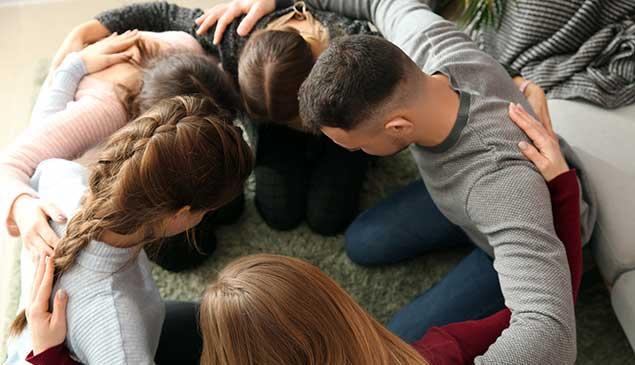 Gruppe junger Menschen betet zusammen