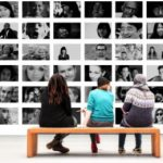drei Menschen reden miteinander vor Wand mit Menschenbilder