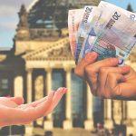 eine Hand gibt Geld weiter