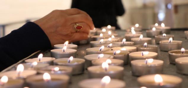 Frau steckt Kerzen in der Kirche an