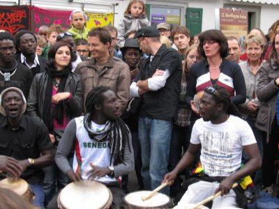Afrikaner spielen vor Menschenmenge mit Trommeln