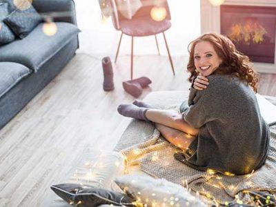 Junge Frau sitzt fröhlich in Ihrem Wohnzimmer