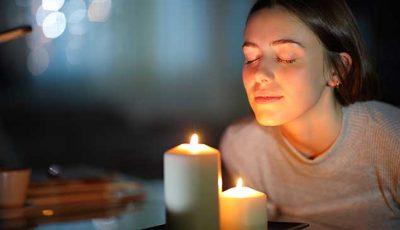 Junge Frau meditiert vor Kerzen